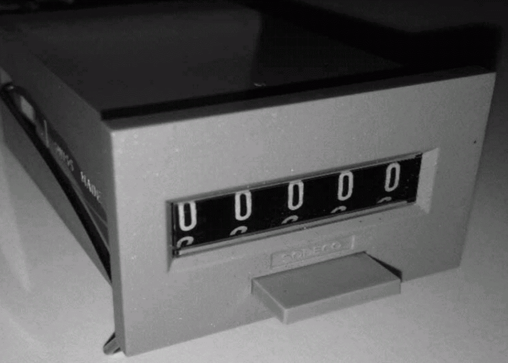 Figure 3. A 5-digit electromechanical Sodeco counter. Although this counter is gray, most of them were black. The legend SWISS MADE was carved on the side. The button on the front is a manual reset. Electromechanical counters were first mentioned in JEAB in a research paper by Conrad, Sidman, and Herrnstein (1958).